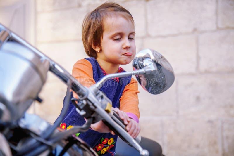 Retrato divertido de poca muchacha del ni?o del motorista que mira en el espejo retrovisor y que se divierte en la motocicleta fo fotografía de archivo