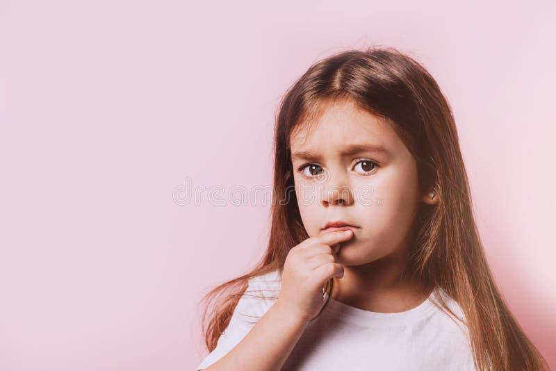 Retrato divertido de poca muchacha de la duda en fondo rosado fotos de archivo