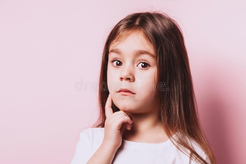 Retrato divertido de poca muchacha de la duda en fondo rosado fotografía de archivo libre de regalías