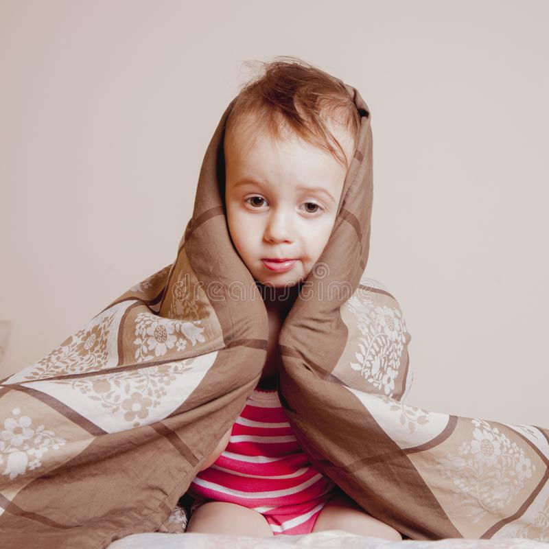 Retrato divertido de poca muchacha linda del niño que se relaja en cama Hora de dormir imagenes de archivo