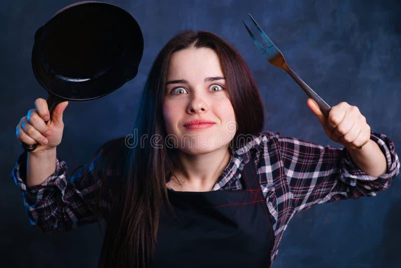 Retrato divertido del ama de casa entusiasta joven con el sartén a imagenes de archivo