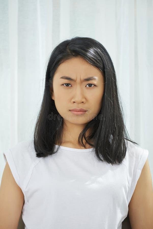Retrato do adolescente asiático olhando de sobrancelhas franzidas fotografia de stock