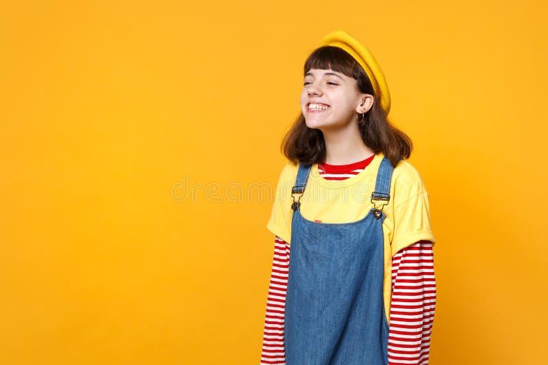 Retrato do adolescente brilhante alegre de sorriso da menina nos sundress franceses da boina e da sarja de Nimes que olham isolad fotos de stock royalty free