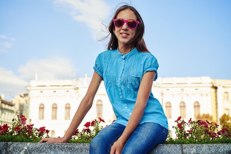 Retrato do adolescente consideravelmente novo no assento cor-de-rosa dos óculos de sol fotografia de stock