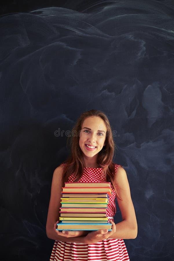 Retrato do adolescente de sorriso bonito contra o quadro-negro ho imagens de stock