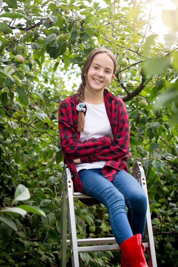 Retrato do adolescente feliz de sorriso que senta-se sobre a escada portátil no jardim fotografia de stock