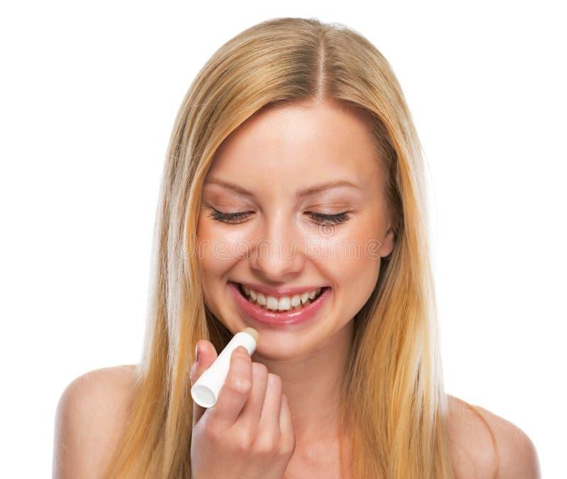 Retrato do adolescente feliz que aplica o batom higiênico fotos de stock