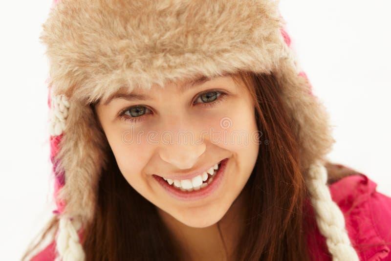 Retrato do adolescente no chapéu forrado a pele desgastando da neve imagem de stock