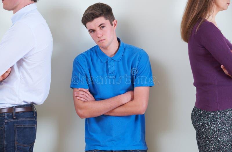 Retrato do adolescente que está entre os pais que são Ignorin foto de stock royalty free