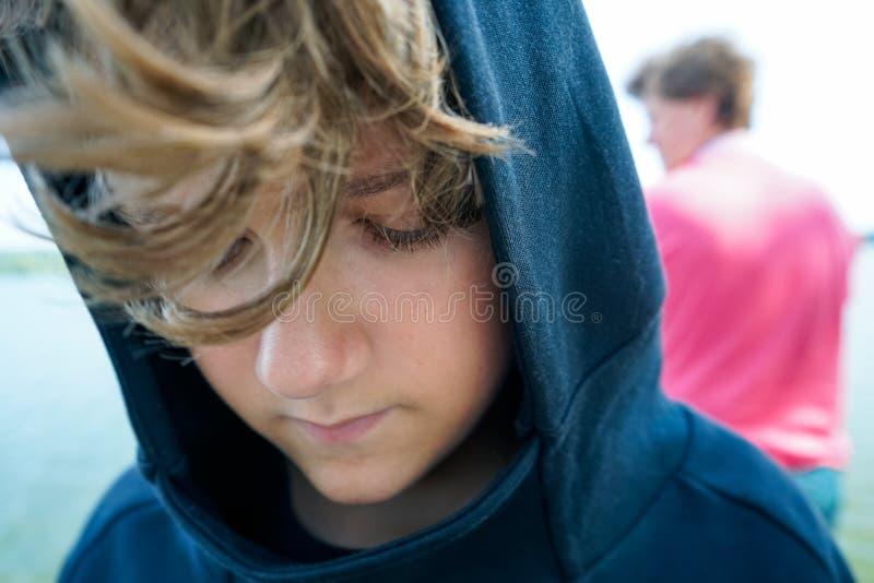 Retrato do adolescente triste e do seu pai no banco do ri fotografia de stock royalty free