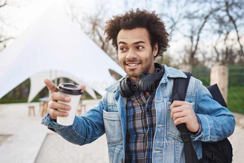 Retrato do afro-americano novo atrativo com o penteado afro que guarda a trouxa e o café, roupa na moda vestindo foto de stock