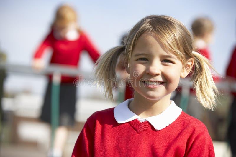 Retrato do aluno fêmea da escola primária no campo de jogos foto de stock