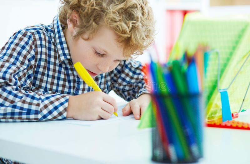 Retrato do aluno na turma escolar que toma notas durante a lição da escrita Educação, infância, trabalhos de casa e conceito da e fotos de stock royalty free
