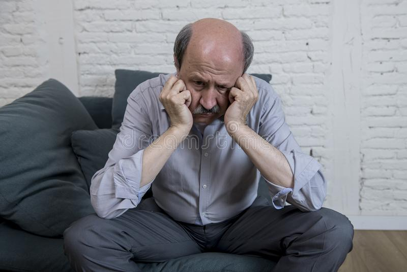 Retrato do ancião maduro superior em sua em casa dor sozinha do sentimento do sofá 60s e na depressão de sofrimento tristes e pre imagens de stock royalty free