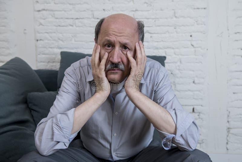 Retrato do ancião maduro superior em sua em casa dor sozinha do sentimento do sofá 60s e na depressão de sofrimento tristes e pre imagens de stock