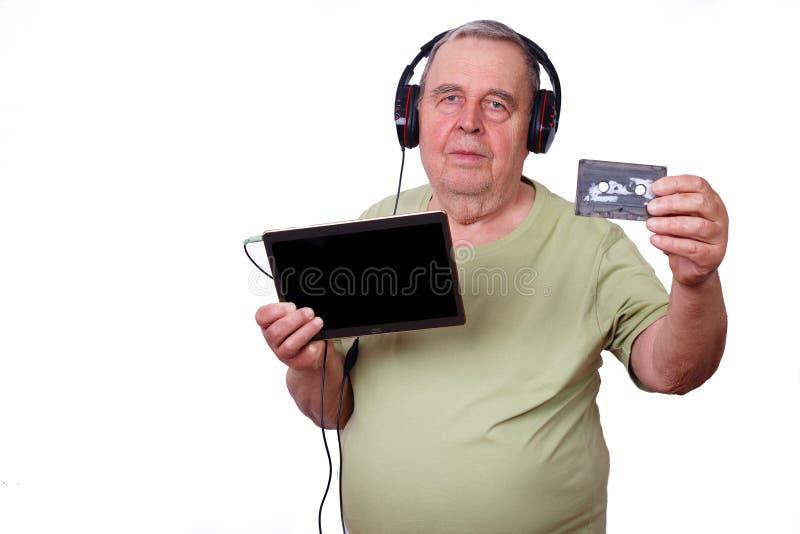 Retrato do ancião que escuta a música nos fones de ouvido usando um tabl foto de stock