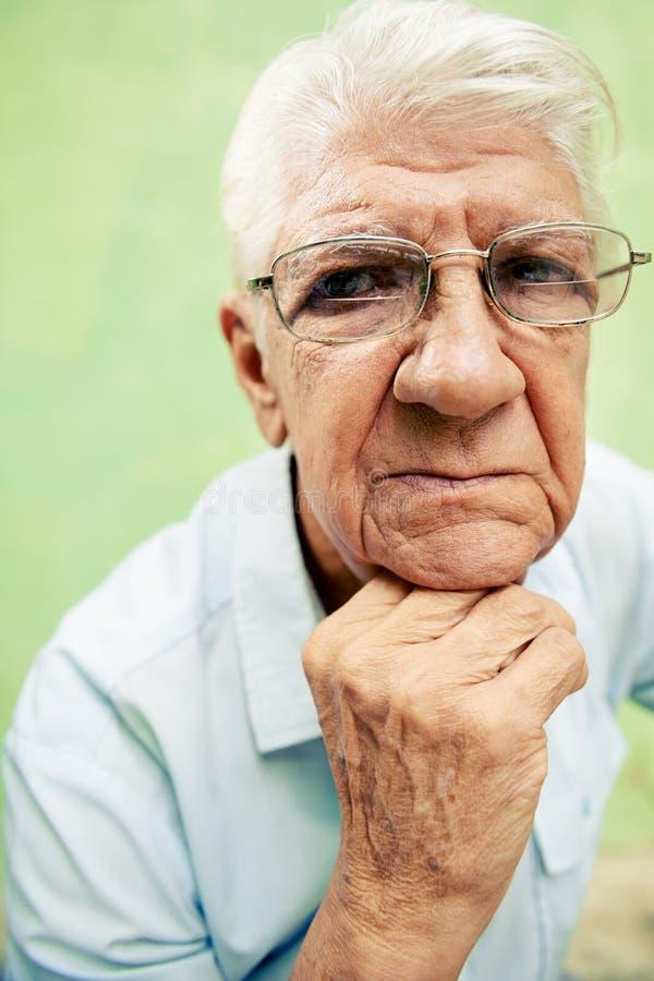Retrato do ancião sério que olha a câmera com mãos no queixo imagem de stock royalty free