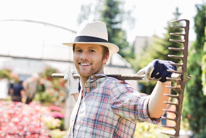 Retrato do ancinho levando de sorriso do jardineiro em ombros no berçário da planta imagem de stock