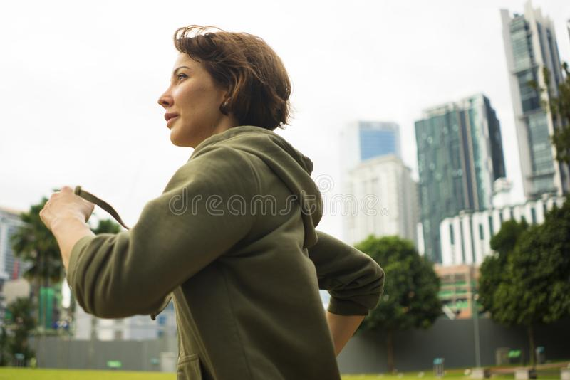 Retrato do ar livre da mulher atrativa e ativa nova do basculador no corredor superior e em movimentar-se do hoodie no exercício  fotos de stock royalty free