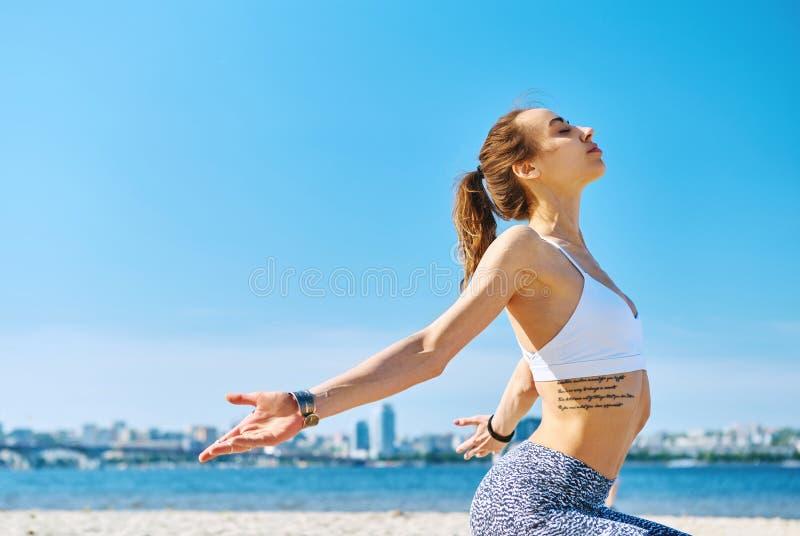 Retrato do ar livre da posição atlética magro nova da mulher no asana da ioga com mãos levantadas na cidade e no céu azul imagem de stock royalty free
