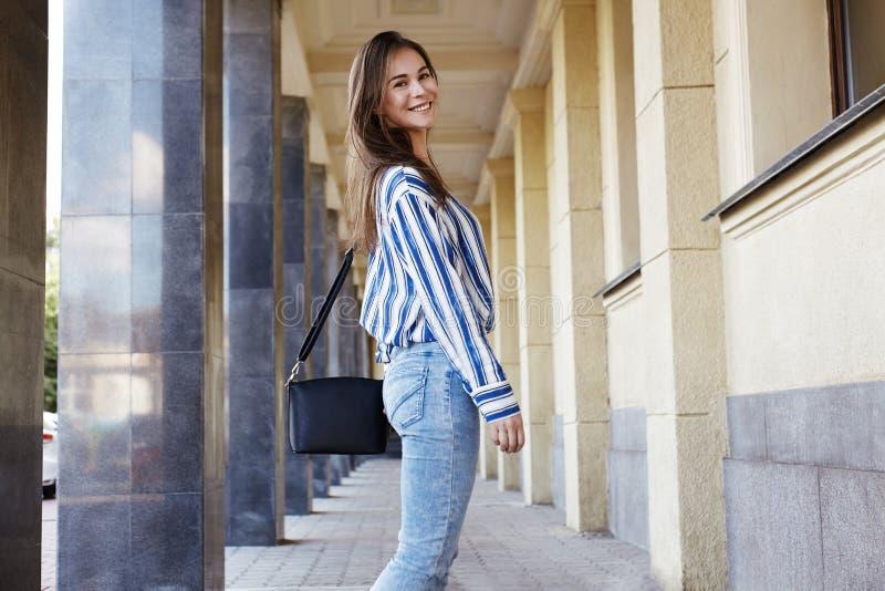 Retrato do ar livre do estilo da rua da menina bonita Forme o sorriso da mulher Ela camisa vestindo da cópia, calças de brim, sac foto de stock
