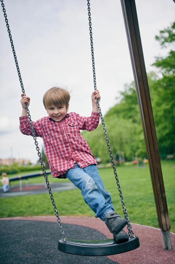 Retrato do ar livre do menino de riso pr?-escolar bonito que balan?a em um balan?o no campo de jogos imagens de stock