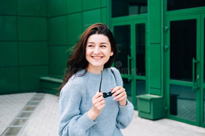 Retrato do ar livre do sorriso moreno novo bonito da menina Menina do moderno do adolescente com os ?culos de sol que vestem o eq imagens de stock
