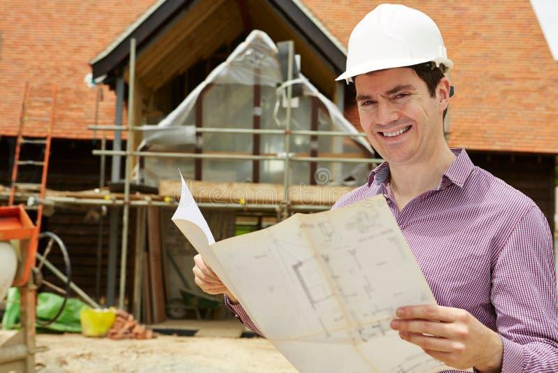 Retrato do arquiteto On Building Site que olha planos da casa imagens de stock royalty free