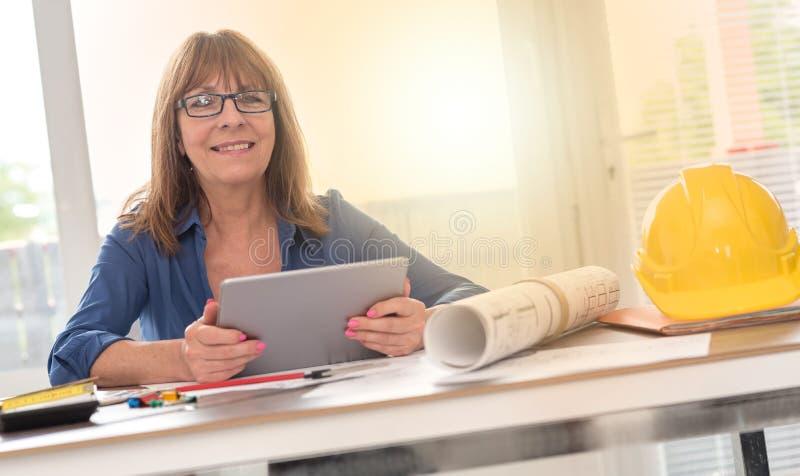 Retrato do arquiteto fêmea que trabalha em planos, efeito da luz imagem de stock