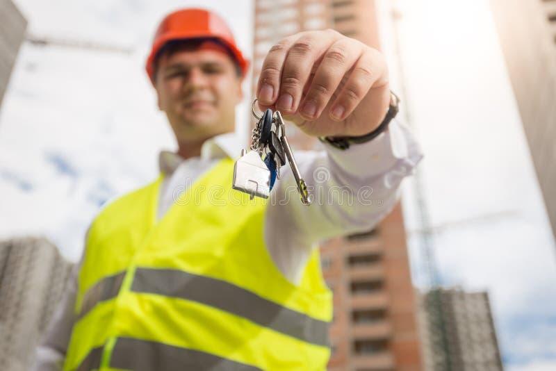 Retrato do arquiteto masculino de sorriso que levanta sobre chaves novas da construção e da terra arrendada nas mãos foto de stock royalty free