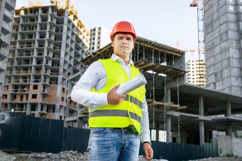 Retrato do arquiteto no capacete de segurança que levanta no terreno de construção imagem de stock