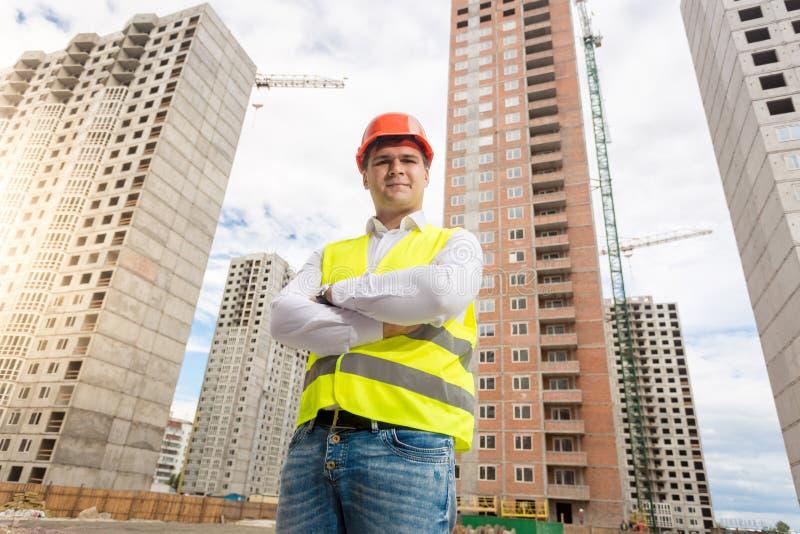 Retrato do arquiteto novo de sorriso no capacete de segurança que levanta no terreno de construção imagens de stock