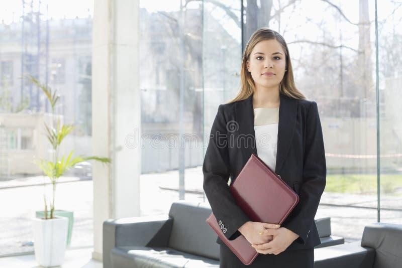 Retrato do arquivo de terra arrendada da mulher de negócios ao estar na entrada do escritório fotos de stock royalty free