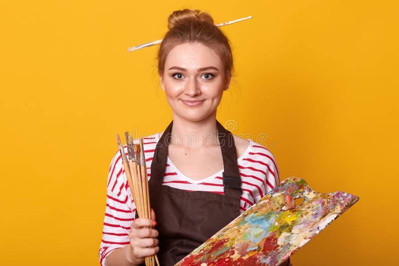 Retrato do artista fêmea novo que guardam escovas e da pintura a óleo na paleta, vestir atrativo da cor da mistura do pintor da m fotos de stock