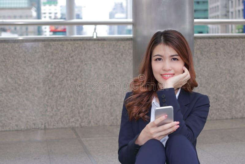 Retrato do asiático novo atrativo que inclina um polo e que olha à câmera na construção urbana contra o fundo do espaço da cópia fotos de stock