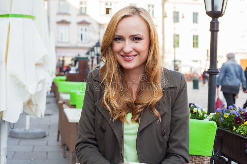 Retrato do assento bonito feliz novo da mulher elegante exterior na imagens de stock royalty free