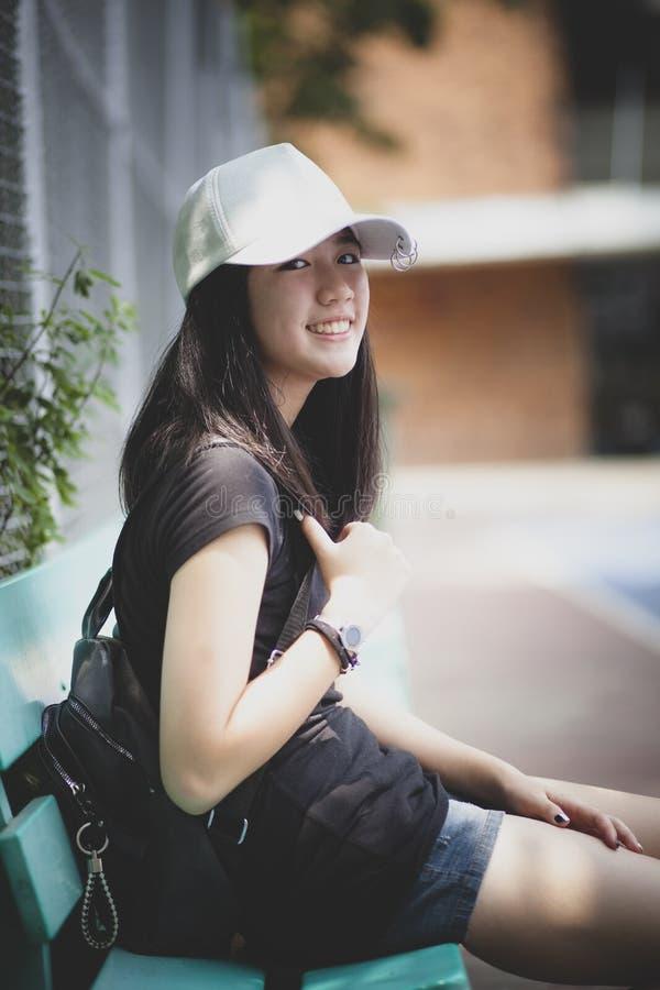 Retrato do assento branco vestindo do tampão do adolescente asiático exterior e da vista com contato de olho à câmera imagens de stock