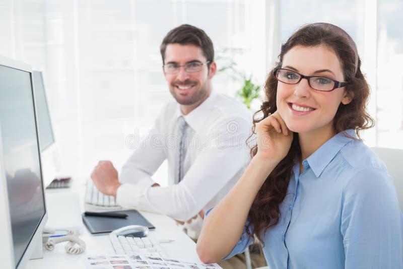 Retrato do assento de sorriso dos colegas de trabalho do negócio imagem de stock