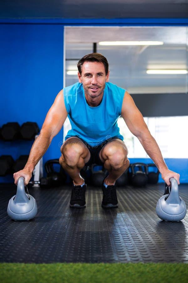 Retrato do atleta de sorriso com kettlebell no gym imagem de stock royalty free