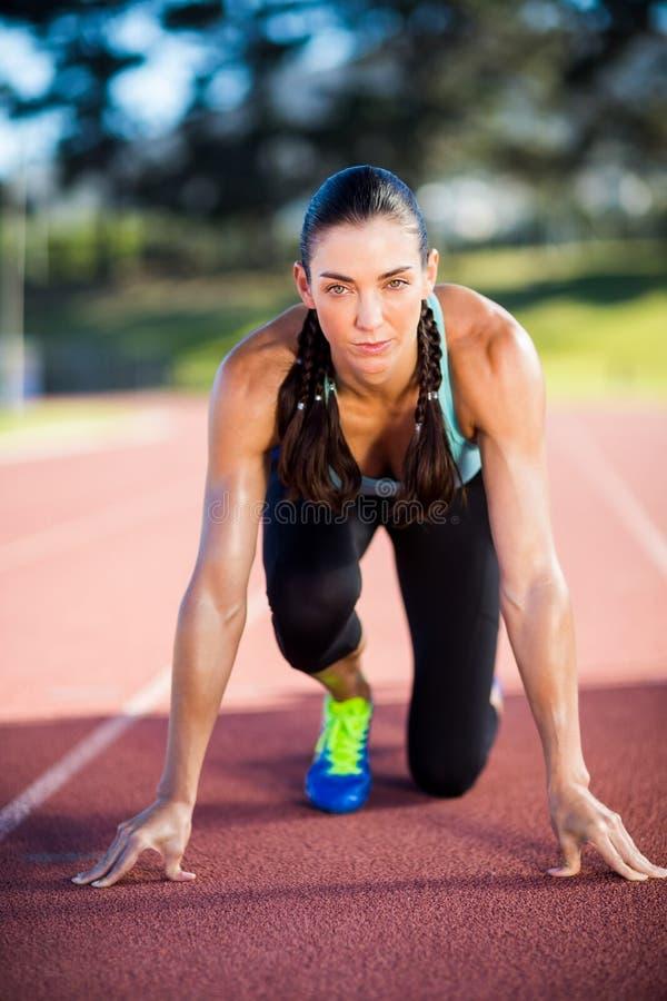 Retrato do atleta fêmea na posição pronto para ser executado foto de stock royalty free