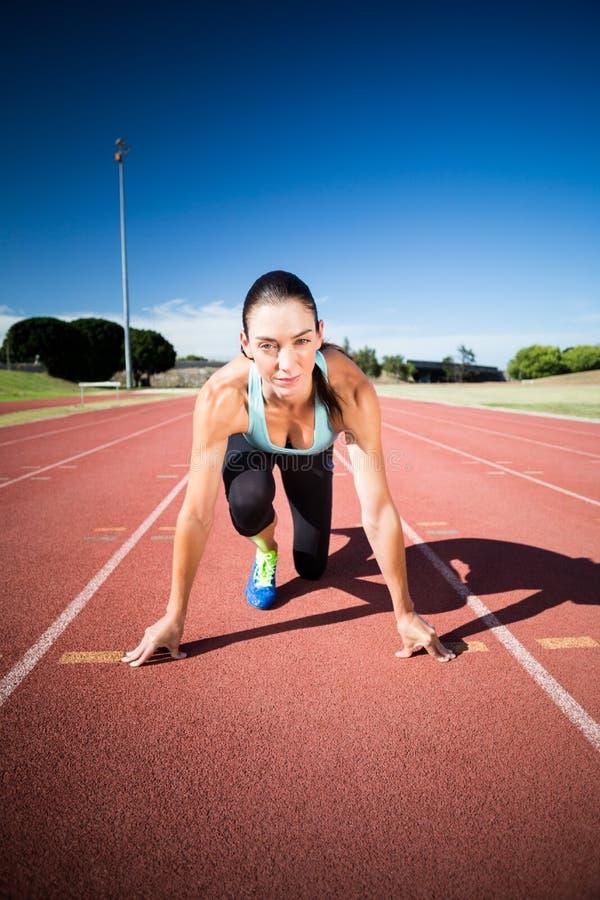 Retrato do atleta fêmea na posição pronto para ser executado foto de stock
