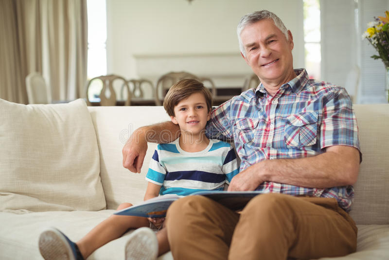 Retrato do avô com seu neto que guarda o livro no sofá imagens de stock