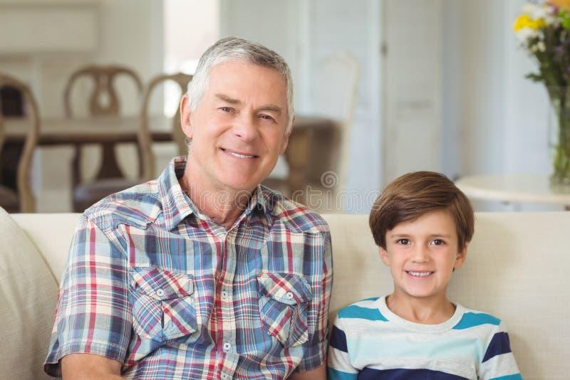Retrato do avô que senta-se com seu neto no sofá fotografia de stock