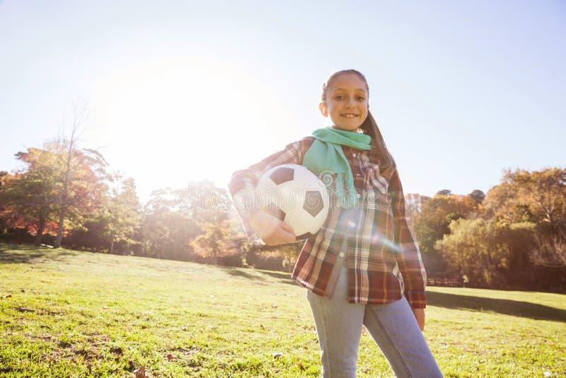 Retrato do baixo ângulo da menina de sorriso que guarda a bola de futebol no parque imagem de stock royalty free