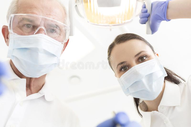 Retrato do baixo ângulo dos colegas que vestem máscaras na clínica dental fotografia de stock