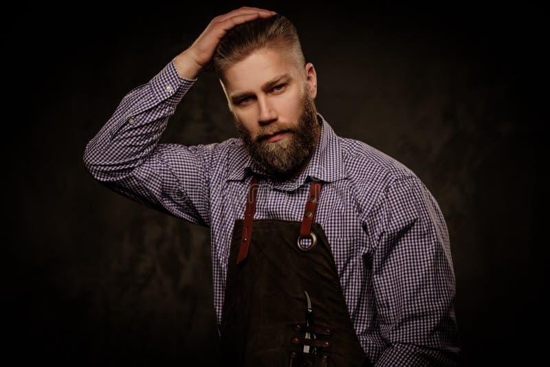 Retrato do barbeiro à moda com a barba e as ferramentas profissionais isoladas em um fundo escuro imagem de stock