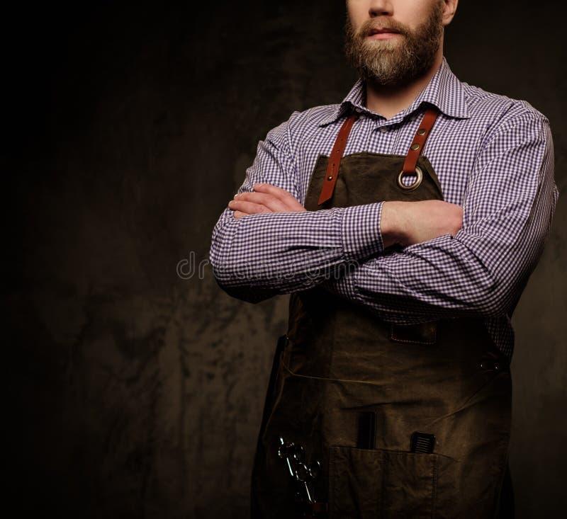 Retrato do barbeiro à moda com a barba e as ferramentas profissionais isoladas em um fundo escuro fotos de stock