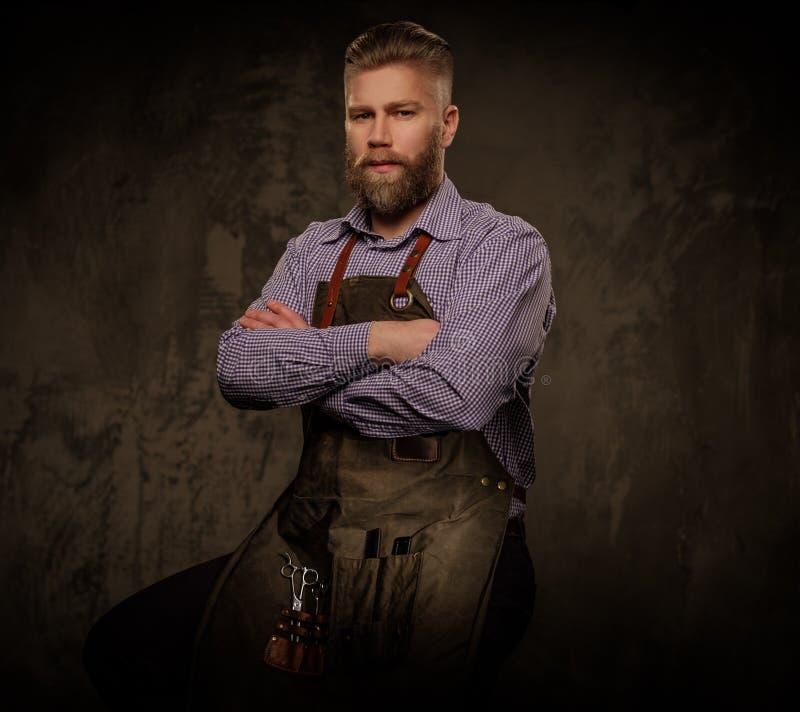 Retrato do barbeiro à moda com a barba e as ferramentas profissionais isoladas em um fundo escuro fotografia de stock