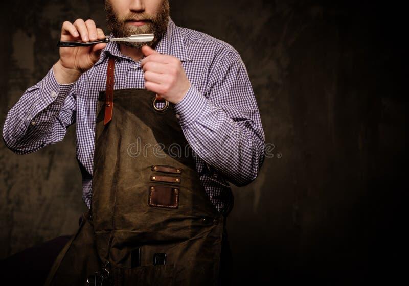 Retrato do barbeiro à moda com a barba e as ferramentas profissionais isoladas em um fundo escuro imagens de stock