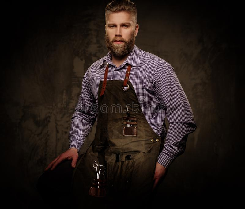 Retrato do barbeiro à moda com barba e de ferramentas profissionais em um fundo escuro fotografia de stock royalty free